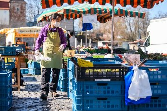 (200401) -- ERFURT (GERMANY), April 1, 2020 (Xinhua) -- A vendor wearing a face mask is seen at a market in Erfurt, central Germany, on April 1, 2020. Germany will extend the restrictions on social contacts to April 19 at the earliest, in a bid to contain the COVID-19 spreading, Chancellor Angela Merkel said following a video conference with minister-presidents of all 16 federal states. (Photo by Kevin Voigt/Xinhua)