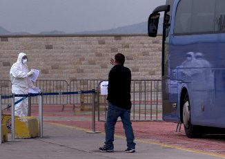 """(200403) -- PIRAEUS (GREECE), April 3, 2020 (Xinhua) -- A medical worker stands next to a bus transporting passengers, who tested negative for COVID-19, of the Greek ferry """"Eleftherios Venizelos,"""" in Piraeus, Greece, on April 3, 2020. The Greek ferry """"Eleftherios Venizelos"""" with 119 confirmed cases on board has docked at Piraeus port, as the Greek government started on Friday the transfer to the shore of 261 passengers who tested negative for the COVID-19, Greek national news agency AMNA reported. (Xinhua/Marios Lolos)"""