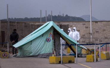 """(200403) -- PIRAEUS (GREECE), April 3, 2020 (Xinhua) -- Medical workers are seen by a tent in Piraeus, Greece, on April 3, 2020. The Greek ferry """"Eleftherios Venizelos"""" with 119 confirmed cases on board has docked at Piraeus port, as the Greek government started on Friday the transfer to the shore of 261 passengers who tested negative for the COVID-19, Greek national news agency AMNA reported. (Xinhua/Marios Lolos)"""