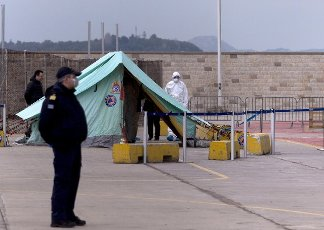 """(200403) -- PIRAEUS (GREECE), April 3, 2020 (Xinhua) -- A coast guard and a medical worker are seen by a tent in Piraeus, Greece, on April 3, 2020. The Greek ferry """"Eleftherios Venizelos"""" with 119 confirmed cases on board has docked at Piraeus port, as the Greek government started on Friday the transfer to the shore of 261 passengers who tested negative for the COVID-19, Greek national news agency AMNA reported. (Xinhua/Marios Lolos)"""