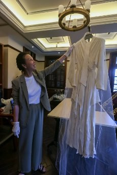 """(200812) -- SHANGHAI, Aug. 12, 2020 (Xinhua) -- Cao Liping, general manager of a laundry, shows a wedding dress after cleaning and maintenance, which was donated by a Jewish refugee to Shanghai Jewish Refugees Museum, in Shanghai, east China, Aug. 11, 2020. A museum dedicated to Jewish refugees in Shanghai is expected to complete its expansion work and open to the public by the end of the year. TO GO WITH """"Shanghai Jewish Refugees Museum to complete expansion this year"""" (Xinhua\/Wang Xiang"""