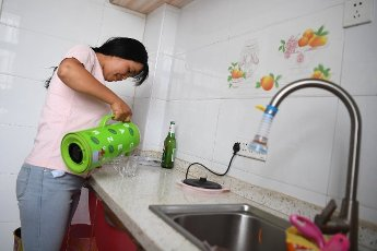 (200812) -- LINXIA, Aug. 12, 2020 (Xinhua) -- Villager Yang Ximei does household chores inside her new home after she was relocated to Tuqiao Township of Linxia County, Linxia Hui Autonomous Prefecture, northwest China\'s Gansu Province, Aug. 11, 2020. In recent years, local authorities in Linxia County have focused on relocation programs as parts of a poverty-alleviation campaign. Livestock breeding, greenhouses, rural tourism and cloth shoes making have been a cornerstone in providing villagers with a financial leg up following their relocation. (Xinhua\/Chen Bin