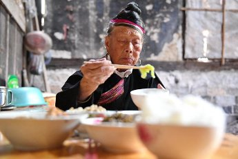 (200812) -- NINGDE, Aug. 12, 2020 (Xinhua) -- Zhong Lianjiao dines at home at Banyueli Village in Xiapu County, southeast China\'s Fujian Province, Aug. 5, 2020. It\'s common to see Zhong Lianjiao, an 89-year-old She ethnic group woman always in traditional She costumes, introduce the cultures of She ethnic group to tourists visiting the ancient Banyueli village. Living in the village for decades of years, Zhong has been making efforts to promote the village\'s tourism by introducing local cultures to tourists. Banyueli is a village where cultural relics and folk customs of She ethnic group are well preserved. (Xinhua\/Lin Shanchuan