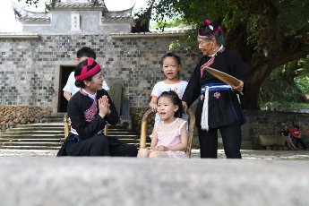 (200812) -- NINGDE, Aug. 12, 2020 (Xinhua) -- Zhong Lianjiao (1st R) sings She ethnic group songs with children at Banyueli Village in Xiapu County, southeast China\'s Fujian Province, Aug. 5, 2020. It\'s common to see Zhong Lianjiao, an 89-year-old She ethnic group woman always in traditional She costumes, introduce the cultures of She ethnic group to tourists visiting the ancient Banyueli village. Living in the village for decades of years, Zhong has been making efforts to promote the village\'s tourism by introducing local cultures to tourists. Banyueli is a village where cultural relics and folk customs of She ethnic group are well preserved. (Xinhua\/Lin Shanchuan