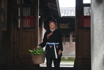 (200812) -- NINGDE, Aug. 12, 2020 (Xinhua) -- Zhong Lianjiao walks out of her home at Banyueli Village in Xiapu County, southeast China\'s Fujian Province, Aug. 5, 2020. It\'s common to see Zhong Lianjiao, an 89-year-old She ethnic group woman always in traditional She costumes, introduce the cultures of She ethnic group to tourists visiting the ancient Banyueli village. Living in the village for decades of years, Zhong has been making efforts to promote the village\'s tourism by introducing local cultures to tourists. Banyueli is a village where cultural relics and folk customs of She ethnic group are well preserved. (Xinhua\/Lin Shanchuan