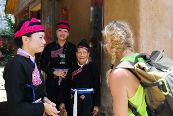 (200812) -- NINGDE, Aug. 12, 2020 (Xinhua) -- Zhong Lianjiao (2nd R) shows She ethnic group costumes to a tourist from Germany at Banyueli Village in Xiapu County, southeast China\'s Fujian Province, Aug. 5, 2020. It\'s common to see Zhong Lianjiao, an 89-year-old She ethnic group woman always in traditional She costumes, introduce the cultures of She ethnic group to tourists visiting the ancient Banyueli village. Living in the village for decades of years, Zhong has been making efforts to promote the village\'s tourism by introducing local cultures to tourists. Banyueli is a village where cultural relics and folk customs of She ethnic group are well preserved. (Xinhua\/Lin Shanchuan