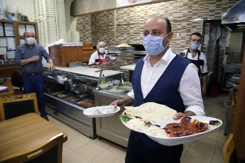 (200812) -- ANKARA, Aug. 12, 2020 (Xinhua) -- A waiter wearing a mask serves meals at a restaurant in Ankara, Turkey, on Aug. 12, 2020. Turkey confirmed 1,212 new COVID-19 cases on Wednesday, raising the total diagnosed cases to 244,392. Meanwhile, 18 people died in the past 24 hours, taking the death toll to 5,891. A total of 934 patients recovered in the last 24 hours, raising the total recoveries to 227,089 in Turkey since the outbreak. (Photo by Mustafa Kaya\/Xinhua