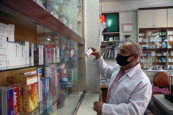 (200812) -- ANKARA, Aug. 12, 2020 (Xinhua) -- A man wearing a mask works at a pharmacy in Ankara, Turkey, on Aug. 12, 2020. Turkey confirmed 1,212 new COVID-19 cases on Wednesday, raising the total diagnosed cases to 244,392. Meanwhile, 18 people died in the past 24 hours, taking the death toll to 5,891. A total of 934 patients recovered in the last 24 hours, raising the total recoveries to 227,089 in Turkey since the outbreak. (Photo by Mustafa Kaya\/Xinhua