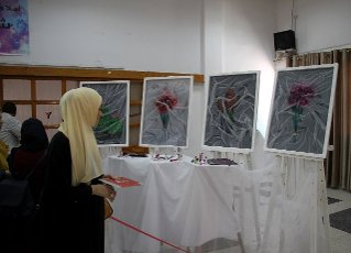 (200812) -- GAZA, Aug. 12, 2020 (Xinhua) -- A woman visits an exhibition of Palestinian artist Kholoud al-Dasooqi in Gaza City, on Aug. 11, 2020. Kholoud al-Dasooqi, a Palestinian artist from the Gaza Strip city of Khan Younis, has opened her two-day exhibition to reveal the violence against women through dozens of paintings. (Photo by Rizek Abdeljawad\/Xinhua) TO GO WITH Feature: Palestinian artist reveals violence against women in Gaza through