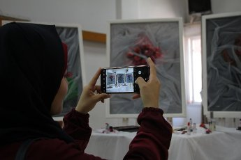 (200812) -- GAZA, Aug. 12, 2020 (Xinhua) -- A woman takes photos of artworks at an exhibition of Palestinian artist Kholoud al-Dasooqi in Gaza City, on Aug. 11, 2020. Kholoud al-Dasooqi, a Palestinian artist from the Gaza Strip city of Khan Younis, has opened her two-day exhibition to reveal the violence against women through dozens of paintings. (Photo by Rizek Abdeljawad\/Xinhua) TO GO WITH Feature: Palestinian artist reveals violence against women in Gaza through
