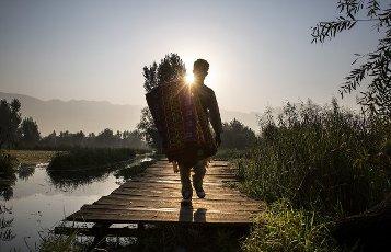 (201001) -- SRINAGAR, Oct. 1, 2020 (Xinhua) -- A vendor carries rugs as he walks on a footbridge during sunrise on the Dal Lake in Srinagar city, the summer capital of Indian-controlled Kashmir, Oct. 1, 2020. (Xinhua\/Javed Dar