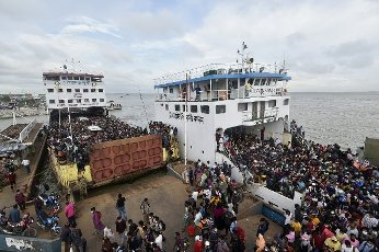 (210731) -- MUNSHIGANJ, July 31, 2021 (Xinhua) -- Two ferries are seen full of passengers at a terminal in Munshiganj on the outskirts of Dhaka, Bangladesh, on July 31, 2021. Thousands of people, mostly garment workers, Saturday used ferries and even walked to reach back to their places of employment in the industrial belts in and around Bangladesh capital Dhaka as the government decided to allow export-oriented factories to resume production on Aug. 1 amid the ongoing COVID-19 lockdown. (Xinhua