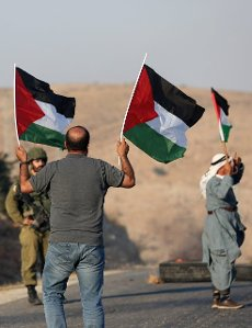 (210731) -- TUBAS, July 31, 2021 (Xinhua) -- Protesters hold Palestinian flags in front of an Israeli soldier during a protest against the expanding of Jewish settlements at Tayasir checkpoint, east of the West Bank city of Tubas, July 31, 2021. (Photo by Ayman Nobani\/Xinhua