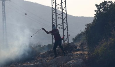 (210731) -- TUBAS, July 31, 2021 (Xinhua) -- A Palestinian protester uses a slingshot to hurl a stone at Israeli soldiers during clashes following a protest against the expanding of Jewish settlements at Tayasir checkpoint, east of the West Bank city of Tubas, July 31, 2021. (Photo by Ayman Nobani\/Xinhua